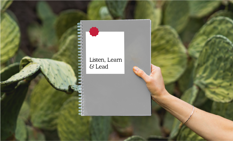 "image of cactuses and a hand holding a notepad in front of it which reads ""Listen, Learn & Lead"""